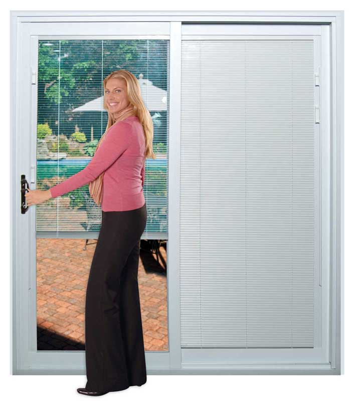 A woman holding a sliding patio door with mini-blinds