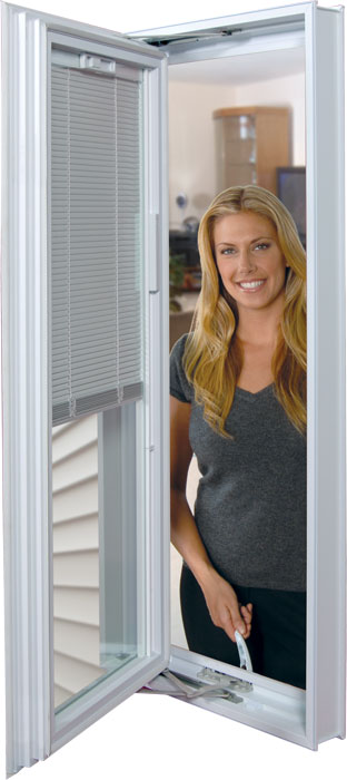 A woman looking through an opened platinum window with mini-blinds.