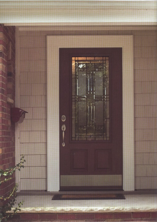 A dark wooden door with decorative glass and metal inside