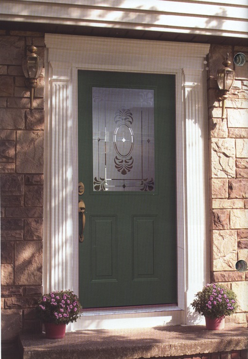 A green door with decorative frosted glass in the upper half