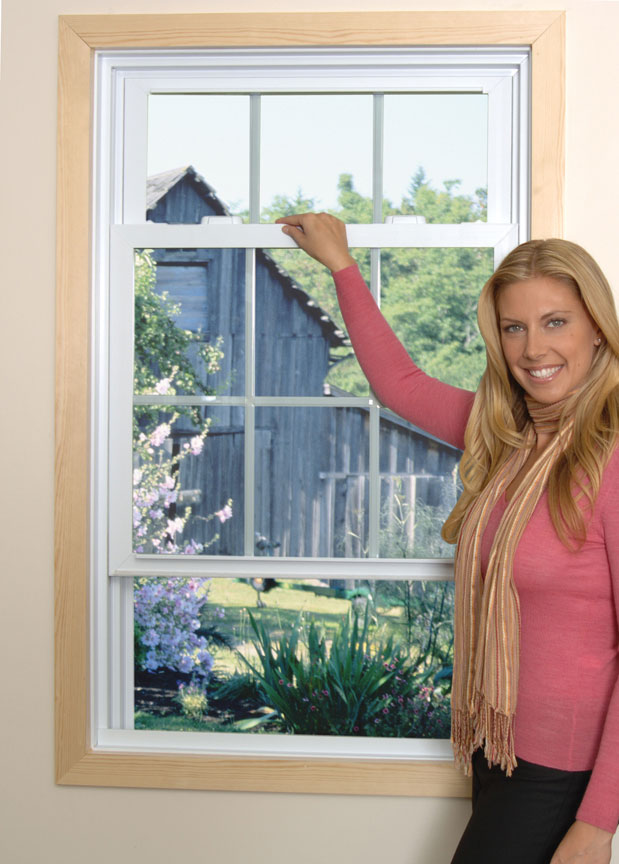 A woman holding a double hung window open.