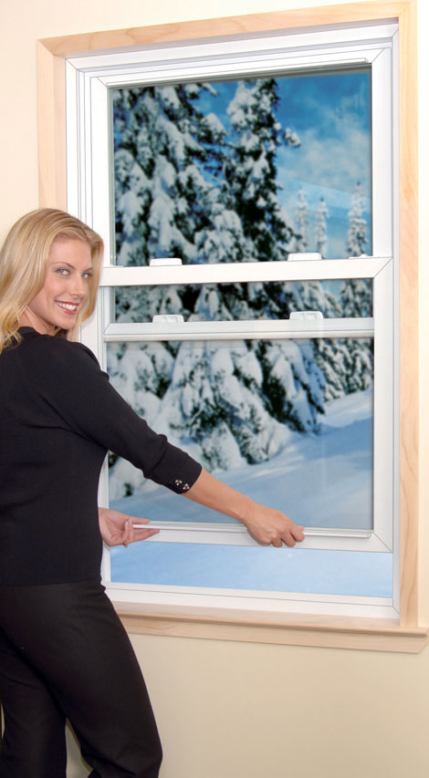 A woman closing a double hung window.