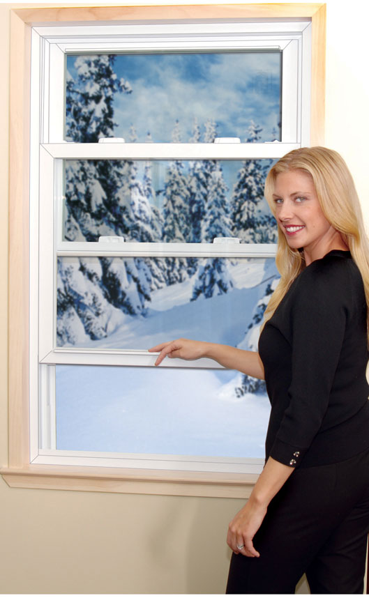 a woman standing next to a double hung window.