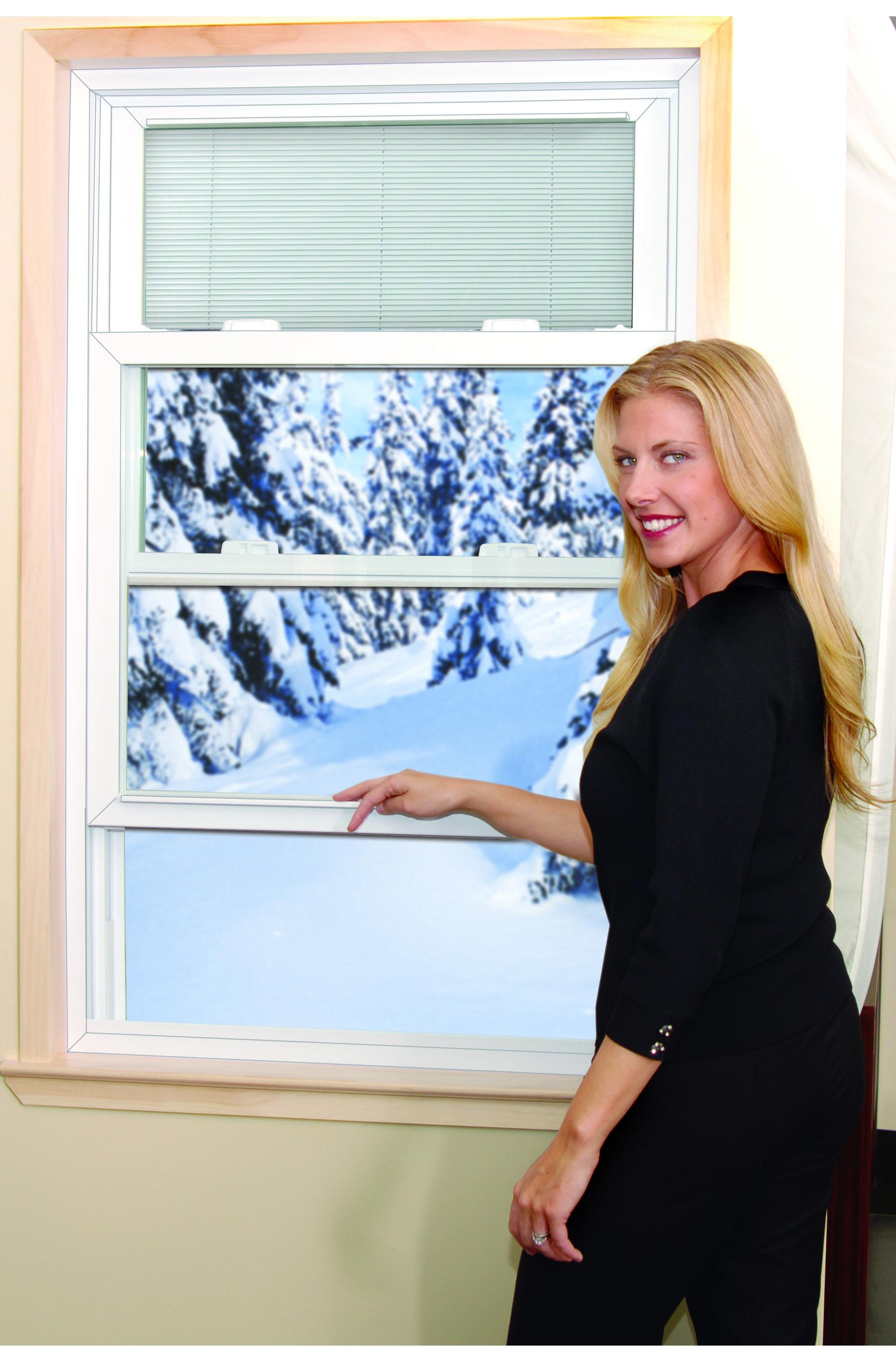 A woman closing an open window.