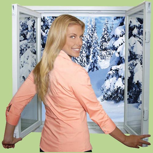 A woman looking over her shoulder in front of an open tilt-n-slide windows with snow outside