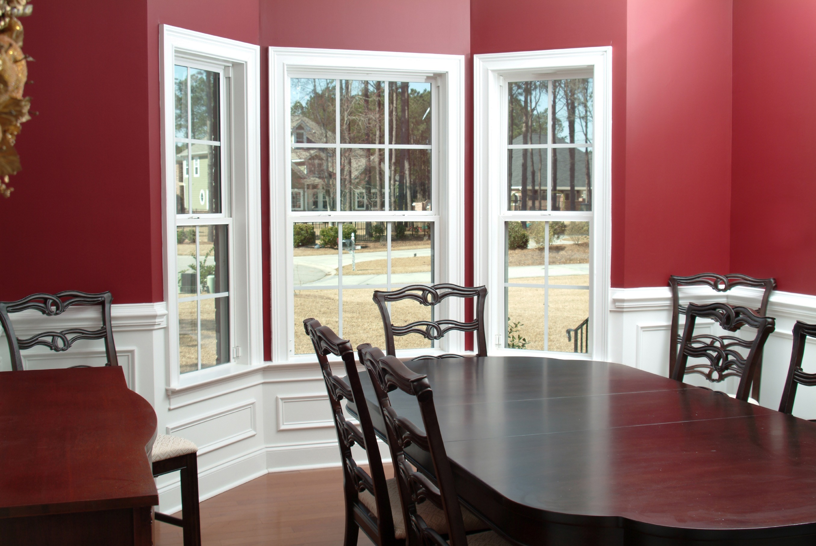 A dining room with three tall windows showing the neighborhood outside.