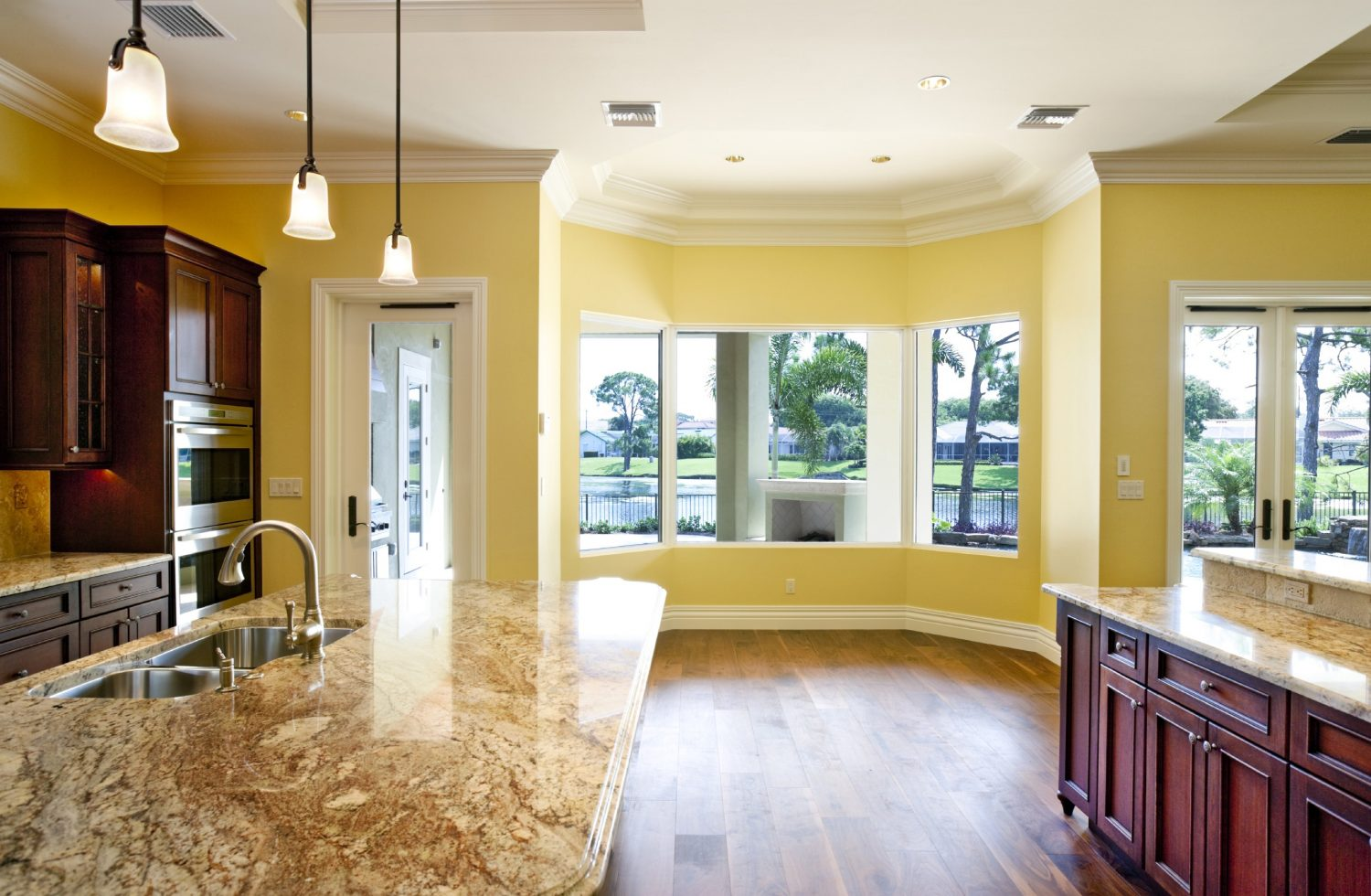 A yellow wall will a bay window looking out onto a neighborhood lake.