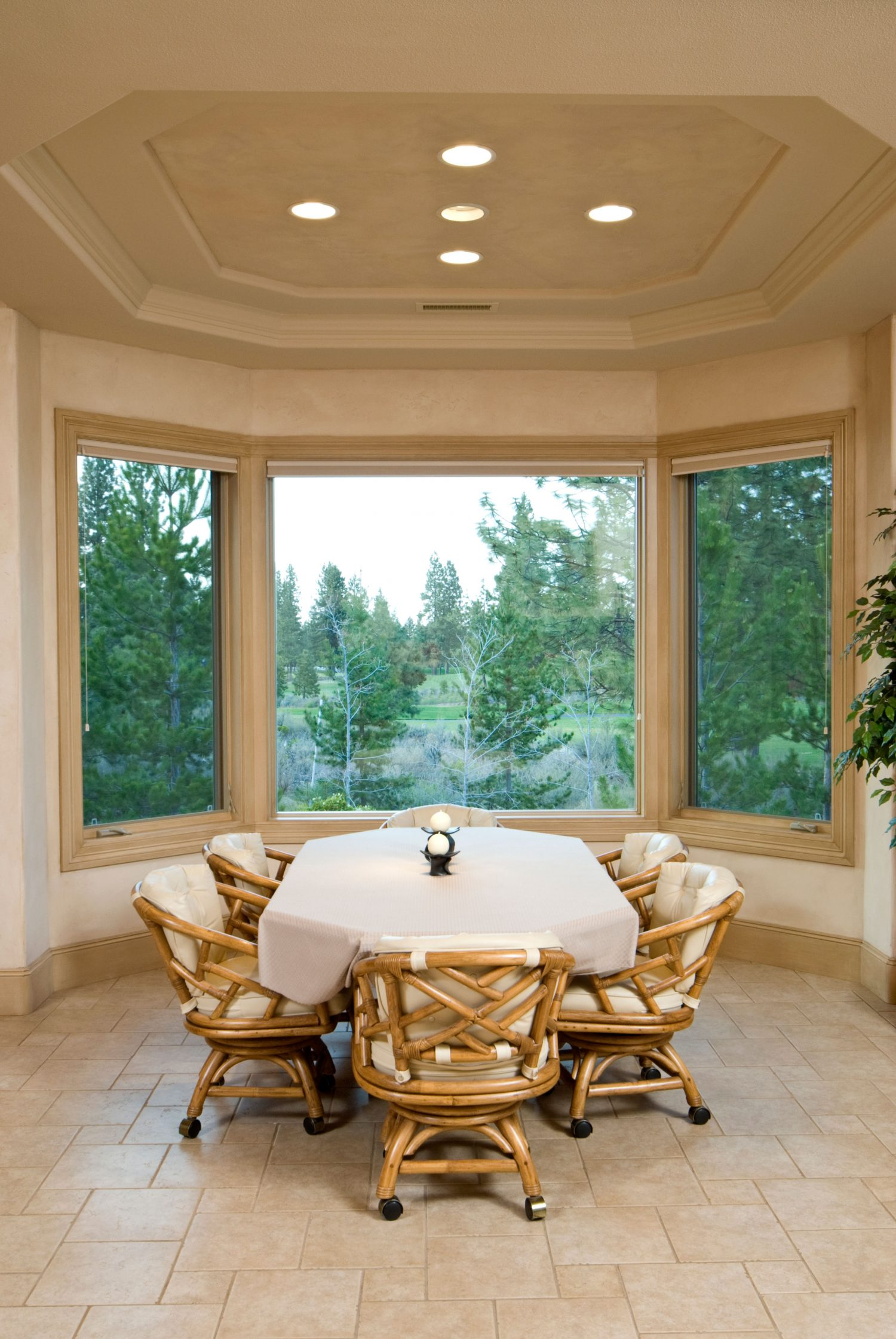 A dining room with large, open windows showing the trees outside the room.
