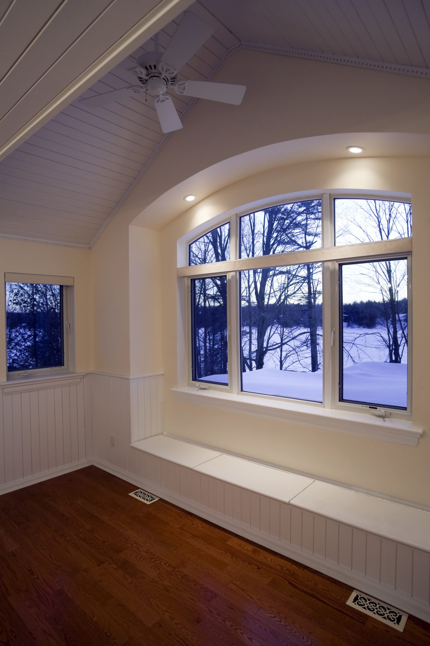 A corner with a large window showing snow outside.