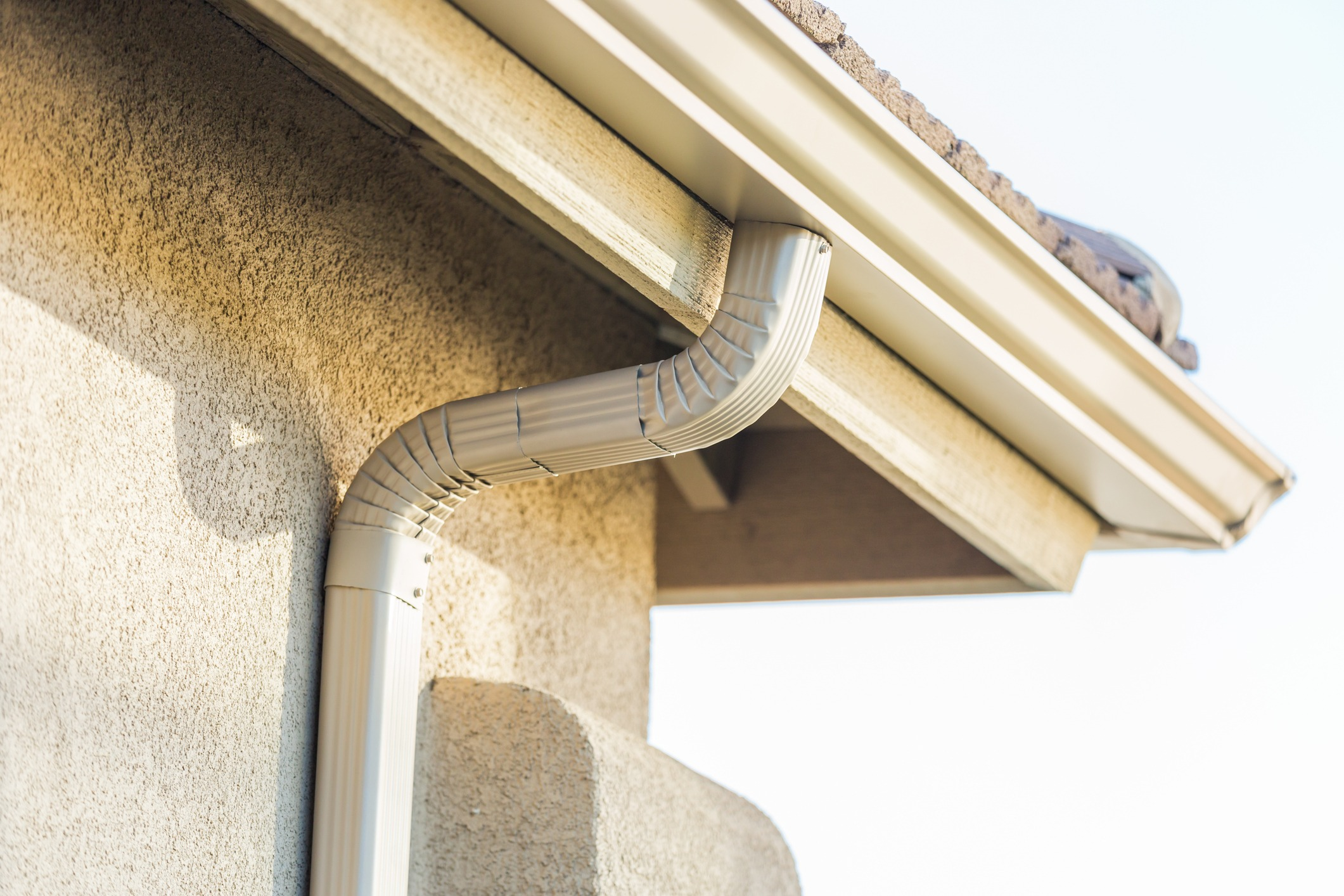 A drain spout going from the roof down the walls of a house