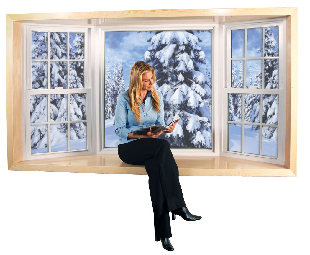 A woman sitting and reading in front of a bay window with snow-covered trees outside.