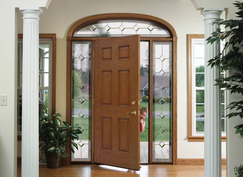 An opened solid wood door surrounded by glass panels with decorative brass caming